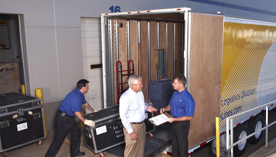 Three men unloading a united van lines truck.