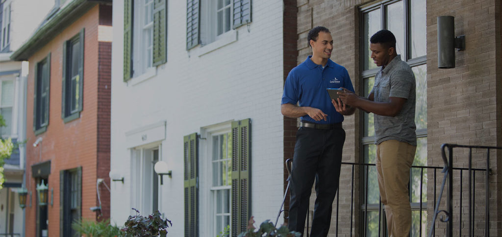 Two men stand on the front porch of a house finishing a corporate relocation.