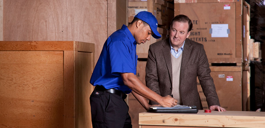 A man in a suit discusses with a mover in a warehouse with crates in the background.