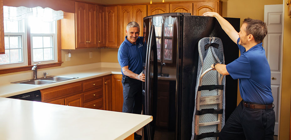 Two movers move a refrigerator out of a kitchen with a dolly.