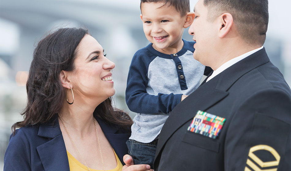 A soldier holds his kid while his wife smiles at him.