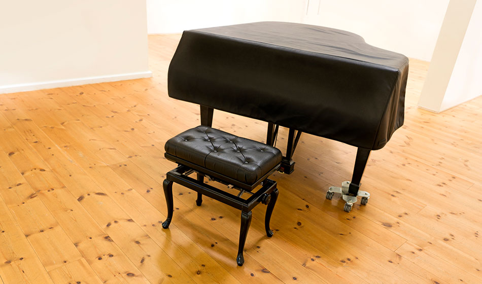 A piano with a bench is sitting in a room.