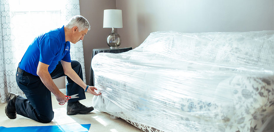 A mover plastic wrapping a sofa.
