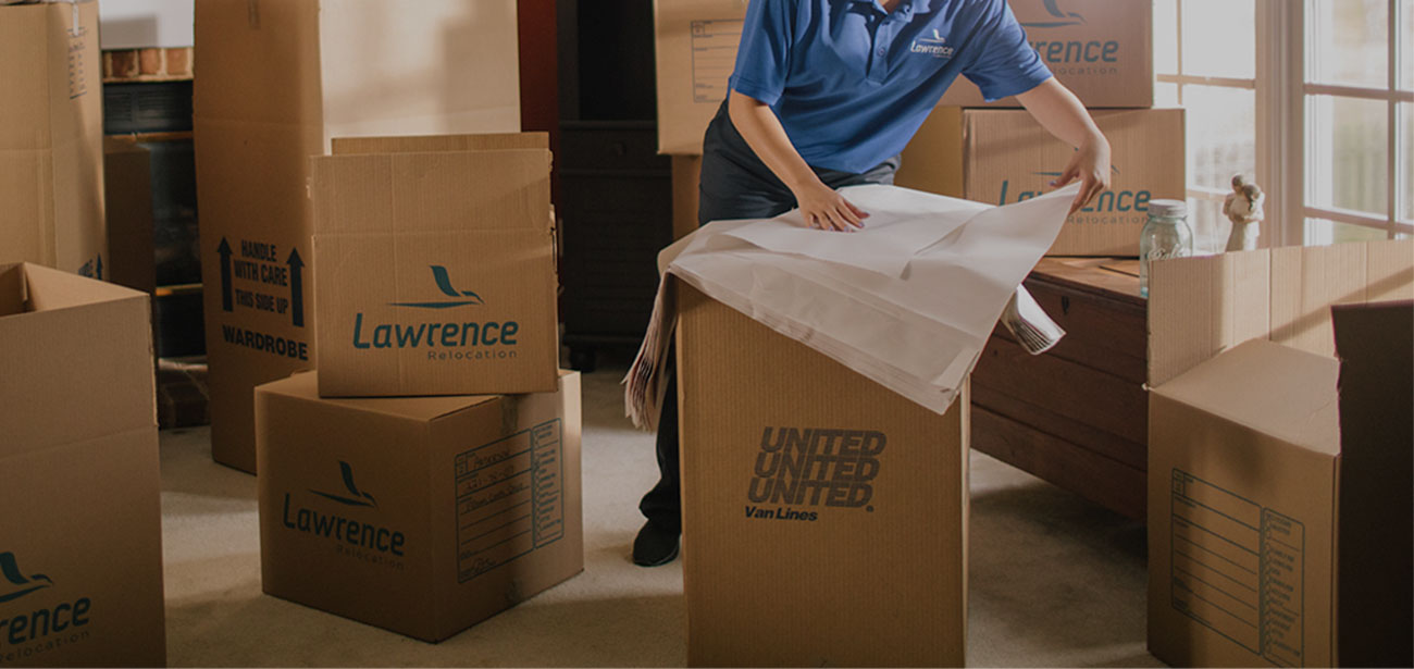 A mover wrapping items to be placed in a box.