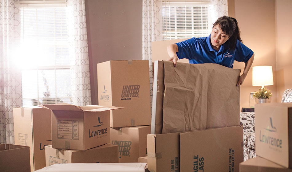 A female mover loads a wrapped package into a box.