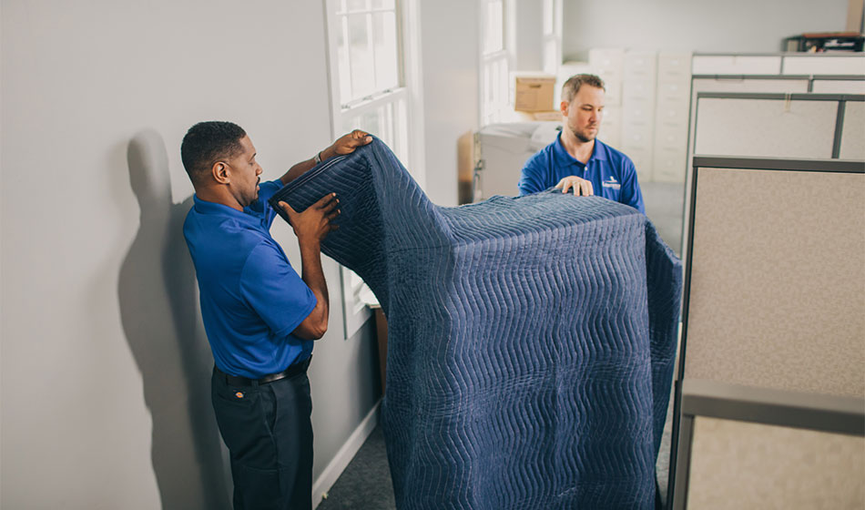 Two movers unwrapping a padded item.