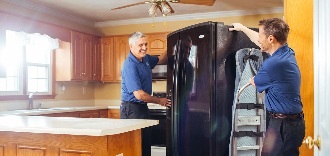 Two movers move a fridge out of a kitchen with a dolly.