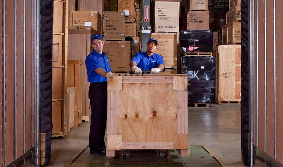 Two movers move a crate in a warehouse.