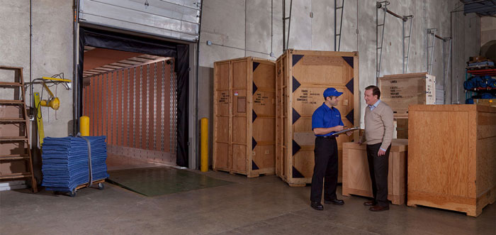 Two movers talk in a warehouse.