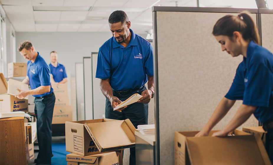A group of movers unload boxes in an office.