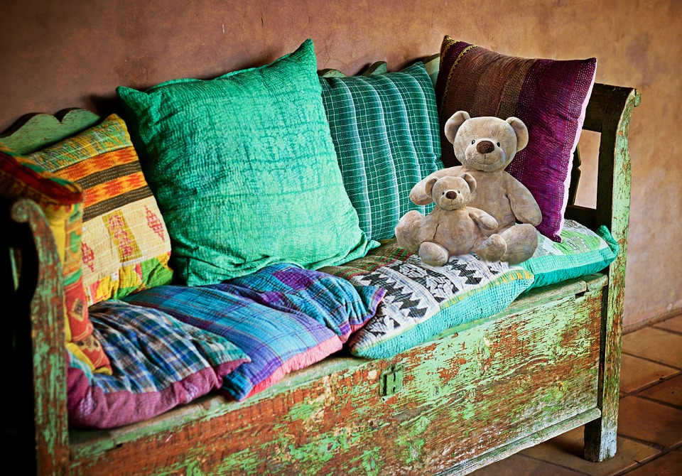 sofa with a baby teddy bear and a large teddy bear leaning against pillows
