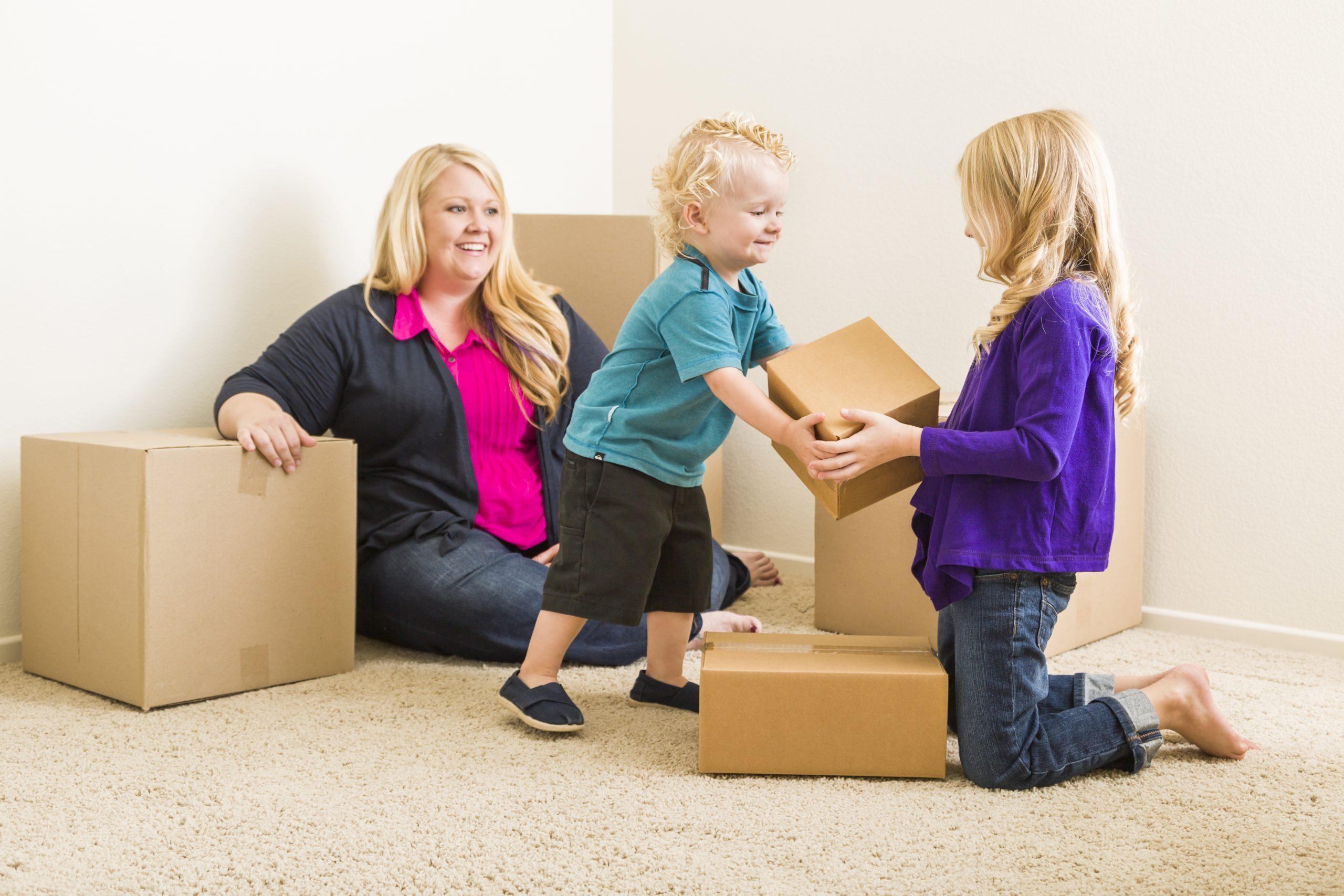 Happy Young Family in Empty Room With Moving Boxes.